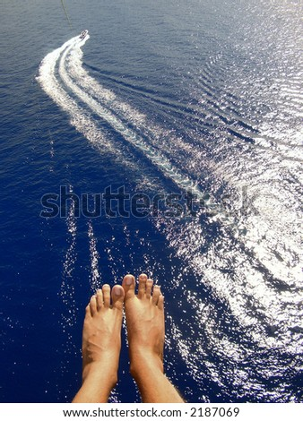 man parasailing over ocean with feet and boat in view