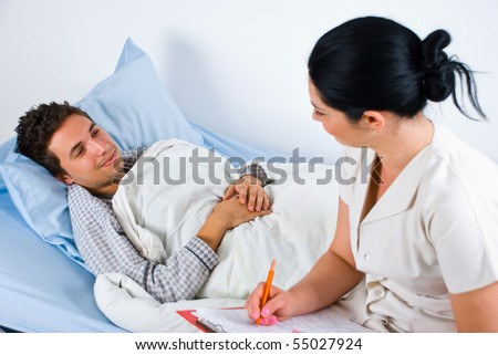 Man patient lying on bed in hospital and having an conversation with his doctor woman