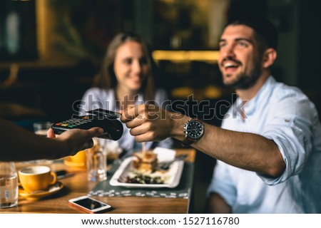 man paying bill at fancy restaurant