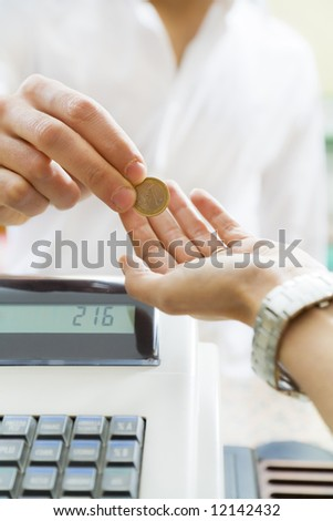 man paying 1 euro to the cashier in a store. Close up of the coin and some copy space