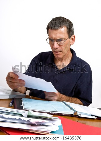 Man paying his monthly bills, looking shocked at a bill he just opened.