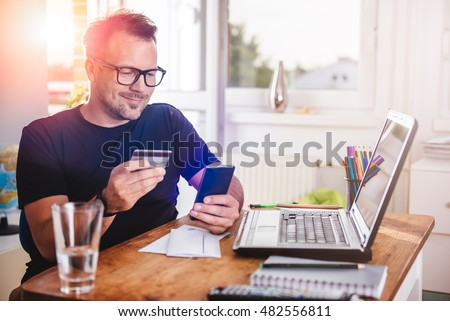 Man paying with credit card on smart phone at home office #482556811
