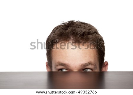 man peaking from under a desk