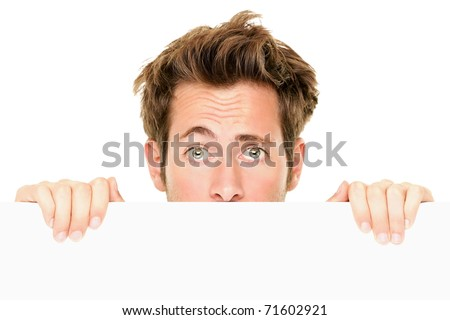 Man peaking showing blank empty white billboard sign surprised. Closeup of young man peeping over white banner edge. Isolated on white background.
