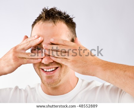 Man peering from behind hands - stock photo