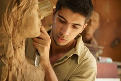Man, people, job, young student at work learning craftsman profession in art class, working with wooden statue and carving wood
