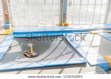 man performs somersault at gym. side view full length photo. copy space #1258762891