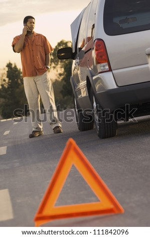 Man phoning with warning triangle in foreground - stock photo
