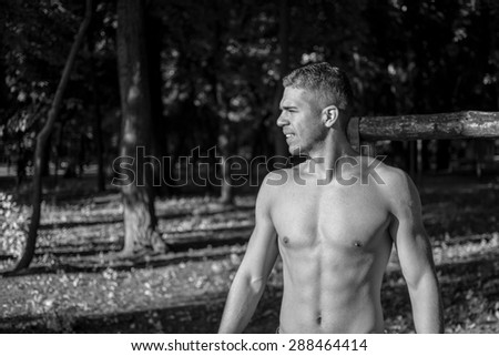 Man photographed in street workout session.Finished one of his exercises and looking towards the sun.Photo was taken in early morning, around 6am in city park Dudova forest. Black and white photo.