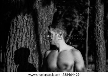 Man photographed in street workout session. Just finished one of his exercises.Photo was taken in early morning, around 6am in city park Dudova forest. Black and white photo.