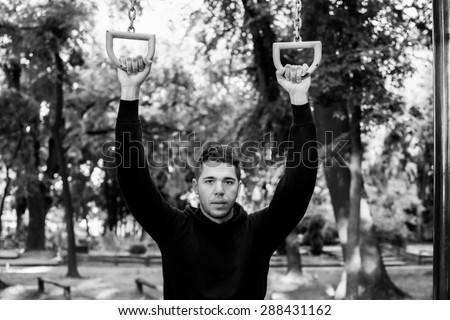 Man photographed in street workout session.Photo was taken in early morning, around 6am in city park Dudova forest. Black and white photo.