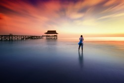 Man photographed sunset near the pier standing in water