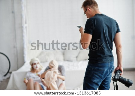 Man photographer shooting on studio two girls while they make their own masks cream. Professional photographer on work and looking at phone for tips.