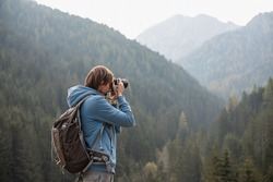 Man photographer taking photographs with digital camera in a mountains. Creative professional photographing. Travel, hobby and active lifestyle concept