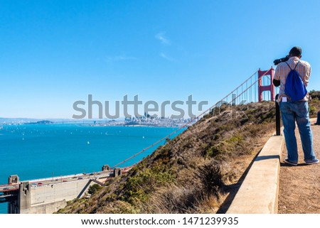 Man/ Photographer/ Tourist taking picture of the iconic Golden Gate Bridge landmark from Battery Spencer near Sausalito city in Marin County opposite the San Francisco city Bay Area in California.
