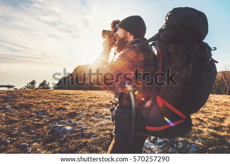 Man photographer with big backpack and camera taking photo of sunset mountains Travel Lifestyle hobby concept adventure active vacations outdoor