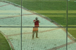 Man photographing himself in a mirrored building with cobbled stones and grass.