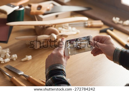 Man photographing his handmade wooden toy airplane with a smart phone on a work table