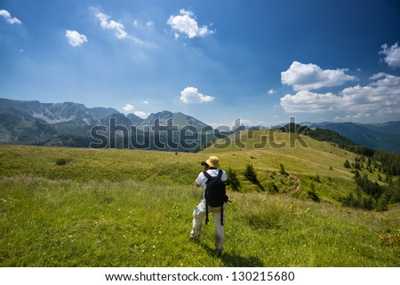 Man photographing in nature. He is taking a picture with camera in a nature.