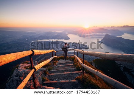 Man photographing landscape with lake and mountains at beautiful sunrise. View from Mount Pilatus, Lucerne, Switzerland Foto stock ©