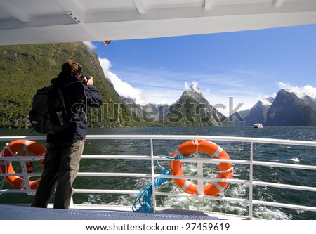 Man Photographing on a Sightseeing Tour Boat in Milford Sound