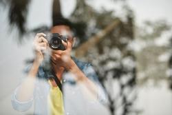 Man photographing something through glass
