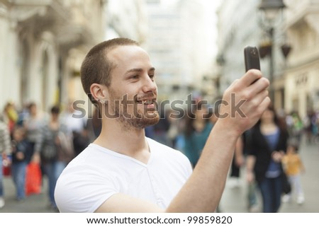 Man photographing with mobile phone walking, background is blured city