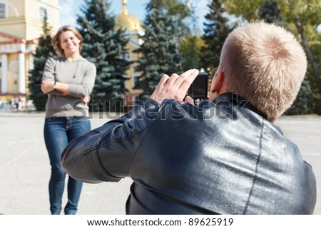 Man photographing young beautiful woman against city`s attractions. Summer time, outdoors. Loving couple