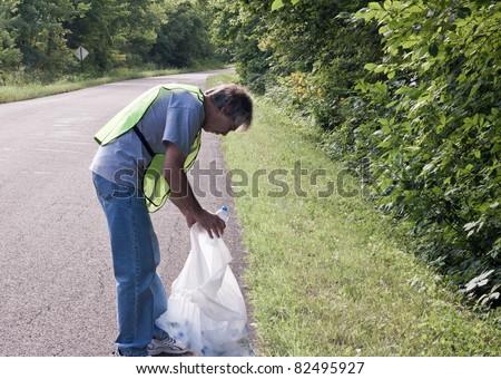 man picking up trash along a rural road