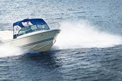 Man piloting motorboat on lake in Georgian Bay, Ontario, Canada.
