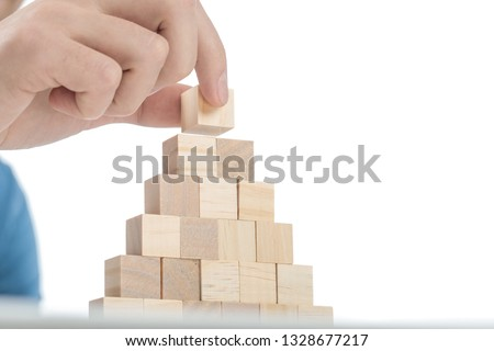 man placing the last brick on top of the stack using only two fingers #1328677217