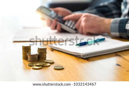 Man planning family finance and using calculator. Counting savings, budget, taxes, expenses and living cost. Calculating money. Accountant working on table and desk.