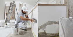 man plasterer construction worker at work, takes plaster from bucket and puts it on trowel to plastering the wall, wears helmet inside the building site of a house