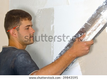 Man plastering the wall with a large spatula