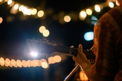 Man play acoustic guitar at outdoor concert with a microphone stand in the front, musical concept.