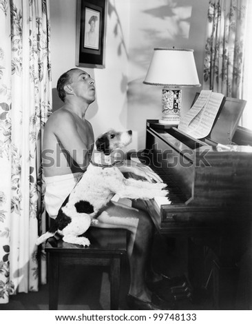 Man playing a piano with his dog next to him