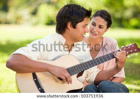 Man playing a song on the guitar while his smiling friend watches him as they are both sitting on the grass