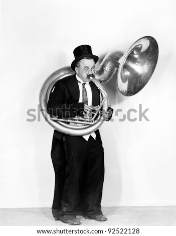 Man playing a tuba in a top hat