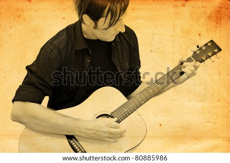 Man playing acoustic guitar against grungy background
