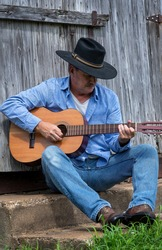 Man playing acoustic guitar alone outdoors sitting in front of old gray country wood barn wearing cowboy hat, rural country, farm, ranch, vintage, independent, musician, music, musical instrument,