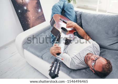 Man playing acoustic guitar in the living room. #1546496465