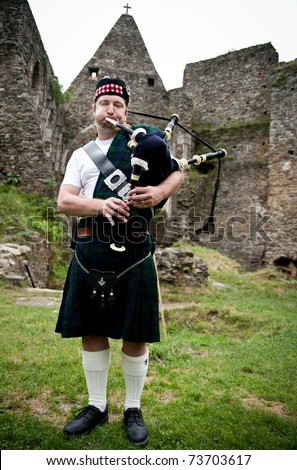 Man playing bagpipe in an old castle