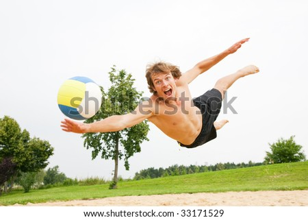 Man playing beach volleyball diving after the ball
