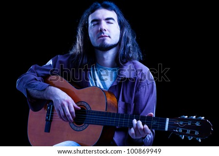 Man Playing Classical Guitar on Black Background
