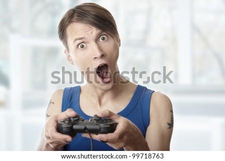 Man playing computer games at home using joystick