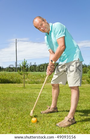 Man playing croquet on cottage