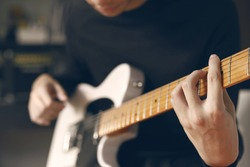 Man playing electric guitar at recording studio.