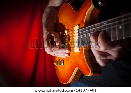 Man playing electric guitar at red background
