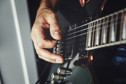 man playing electric guitar close up view, very shallow depth of field image, cinematic effect applied