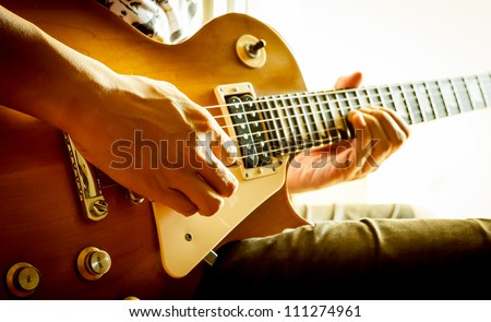 man playing electric guitar with nature light